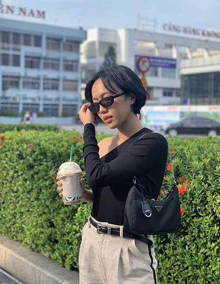 Quỳnh Anh túi đeo vai Prada với váy màu đen